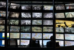 security monitoring control console room with a wall of screens and two workers back silhouettes