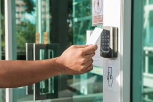 Hand using security key card scanning to open the door to entering private building